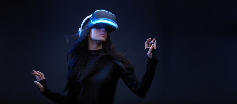 Beautiful woman with flowing hair in futuristic dress over dark background. Girl in glasses of virtual reality. Augmented reality, science, future technology, robots and people concept. VR.