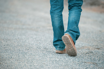 Feet walking of lonely man,step by step on the street.Picture of journey person wearing jean and fashion shoes (boot) along the path strew with rocks