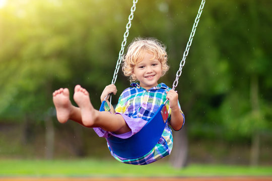 Child on playground. swing Kids play outdoor.