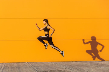 Young satisfied sporty beautiful woman with fit body jumping and running, hurry up against orange wall background. Gymnast jumping high with toothy smile, full length, outdoor