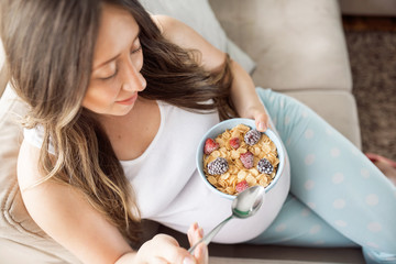 Top view of happy pregnant woman eating cereals with fruits for breakfast in bed at home