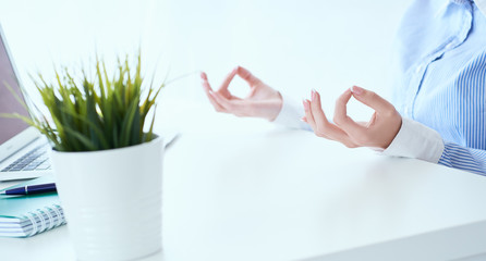 Mid section of calm businesswoman meditating at work, focus on female hands in mudra, close up view. Peaceful mindful employee practicing exercises at workplace.