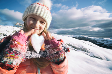 girl holds in her hands a heart of snow