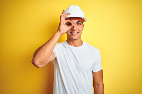 Young handsome man wearing construction helmet over yellow isolated background doing ok gesture with hand smiling, eye looking through fingers with happy face.