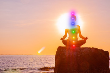 Woman is meditating with glowing seven chakras on stone at sunset. Silhouette of woman is practicing yoga on the beach. Wall mural