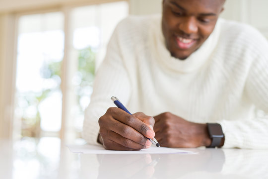 Close up of african man writing a note on a paper smiling confident