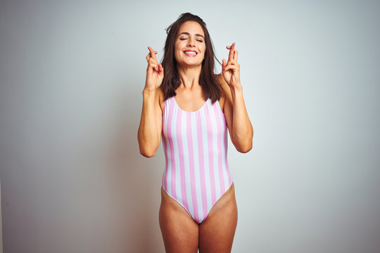 Young beautiful woman wearing striped pink swimsuit swimwear over isolated background gesturing finger crossed smiling with hope and eyes closed. Luck and superstitious concept.