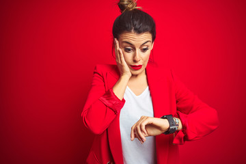 Young beautiful business woman standing over red isolated background Looking at the watch time...