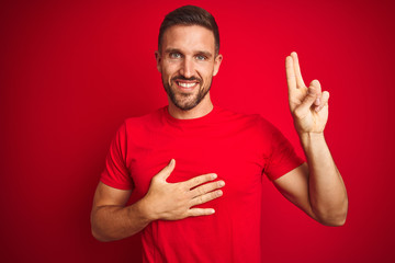 Young handsome man wearing casual t-shirt over red isolated background smiling swearing with hand...