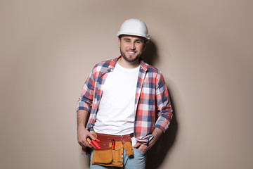 Young working man in hardhat standing on color background