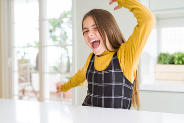 Young beautiful blonde kid girl wearing casual yellow sweater at home Dancing happy and cheerful, smiling moving casual and confident listening to music