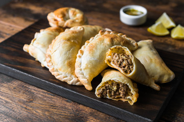 Traditional baked Argentine empanadas savoury pastries with meat beef stuffing against wooden background Fotomurales