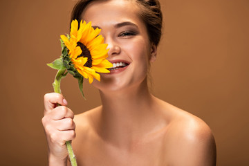 happy laughing beautiful naked woman with yellow sunflower isolated on brown
