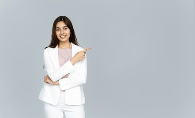 Happy indian young business woman wear white suit looking at camera pointing finger at copy space isolated on grey studio background, smiling beautiful confident hindu lady professional showing aside Wall mural