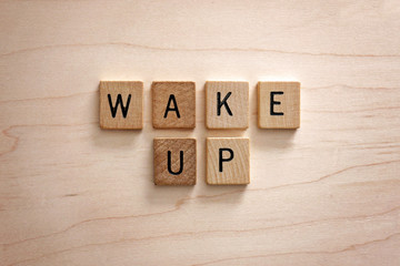 Words Wake Up are Spelled out in Wooden Letter Blocks on a Wood Background