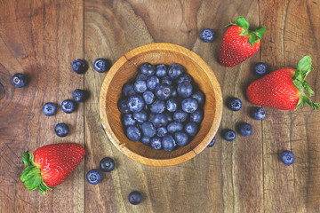 Wooden Bowl of Blueberries with Fresh Strawberries on Rustic Wood Plank Background
