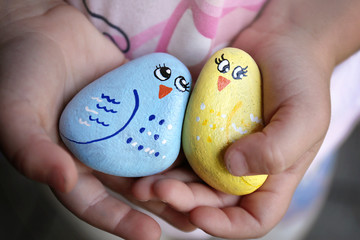 Hands of a Little Child Holding Friendship Rocks Painted like Happy Colorful Birlds
