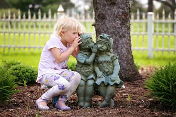 Cute Little Girl Whispering Secret to Little Garden Statue Friends