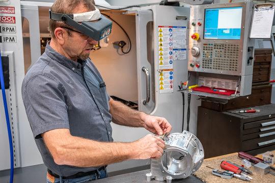 CNC machine operator measuring a part