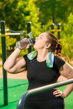 plus size girl drinks clean water from a bottle after sports activities in the park