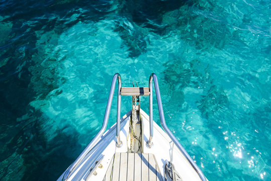 (Selective focus) Stunning view of a bow of a yacht sailing on a beautiful turquoise and transparent sea. Costa Smeralda (Emerald Coast) Sardinia, Italy.