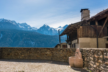 Stone wall, fountain with drinking water and old Italian house, built of wood and stones with snow covered mountains in the background.
