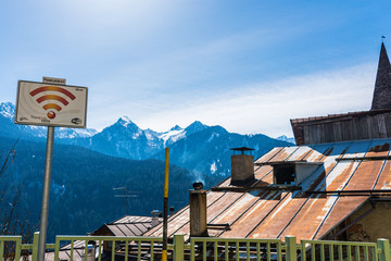 Free WiFi zone sign, tin, rusted roof and snow-capped Italian alpine mountains in the background. Blue sky above.