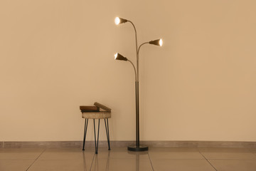 Stylish lamp with table near light wall
