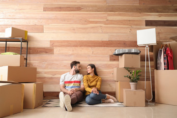 Young couple with belongings after moving into new house Wall mural