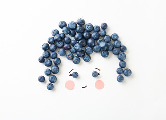 Cute face made of ripe blueberry on white background