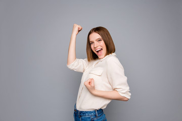 Portrait of cute charming positive cheerful lady raise fists scream shout yeah isolated wear fashionable modern blouse content grey silver background