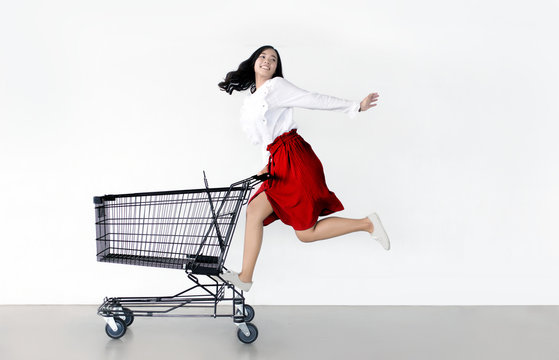 happy asian woman with shopping cart ready for shopping on sale