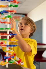 Boy learning science model in classroom