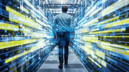 Shot of a Young It Specialist Walking through Corridor in Working Data Center Full of Rack Servers and Supercomputers. Conceptual Visualisation of High Speed Internet Connection with Yellow Lines.