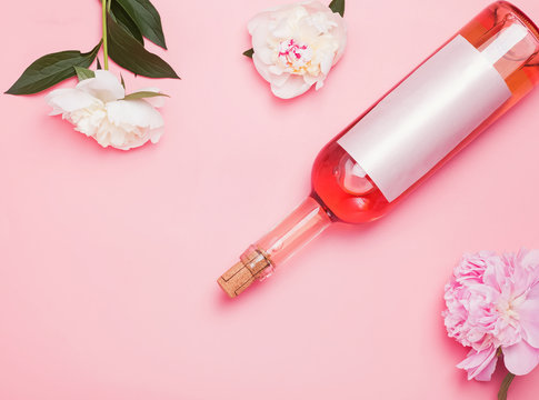 Rose wine and beautiful peonies on the pink background.