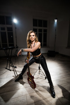 Vocalist in leather clothes sitting in the studio with light and musical instruments.