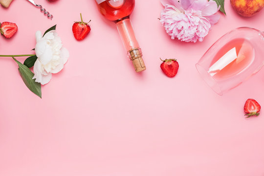 Creative composition with rose wine and delicious strawberries on the pink background
