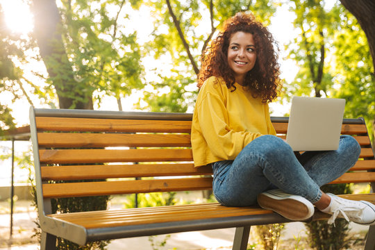 Happy young beautiful curly student girl sitting outdoors in nature park using laptop computer.