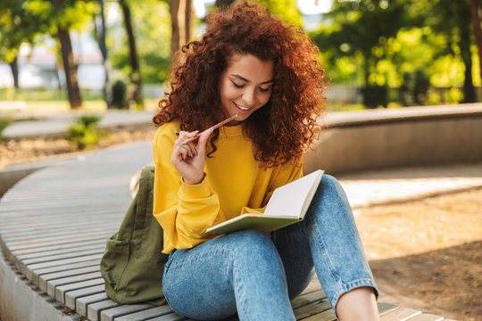 Young beautiful curly student girl sitting outdoors in nature park writing notes in notebook.