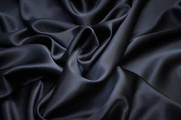 Silk fabric, satin. Black colour. Texture, background, pattern.