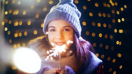 Girl celebrating Christmas with sparkling stick