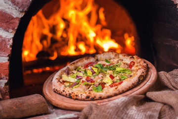 tasty pizza out of oven in restaurant kitchen