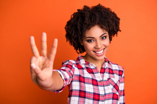 Close-up portrait of her she nice-looking attractive lovely cute cheerful cheery wavy-haired lady wearing checked shirt giving 3 sign isolated over bright vivid shine orange background