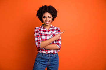 Portrait of her she nice attractive lovely cheerful cheery confident wavy-haired lady wearing checked shirt pointing aside ad advert isolated on bright vivid shine orange background