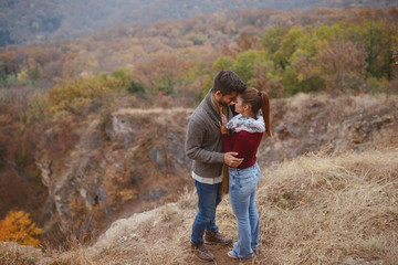 Cute multicultural couple madly in love dressed casual standing at viewpoint in autumn and hugging....