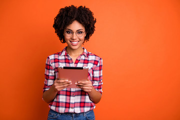 Fototapete - Portrait of nice cute attractive lovely cheerful cheery smart clever wavy-haired lady nerd wearing checked shirt holding in hands digital e-book isolated over bright vivid shine orange background
