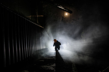Horror scene of a scary children's ghost, Silhouette of scary baby doll on dark foggy background with light.