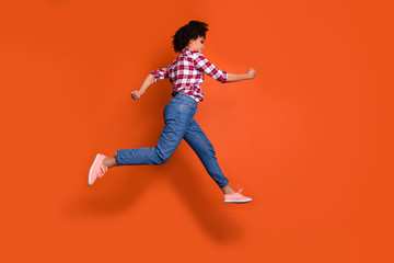 Full length side photo of jumping high athletic lady run shopping sale discount wear jeans denim pants plaid shirt outfit isolated orange background
