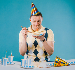 Portrait of man who is celebrating his birthday party, wearing light yellow shirt and party cap on head, making fun, isolated over green background
