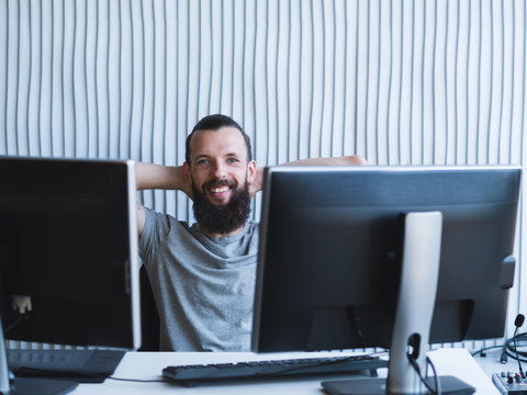 Successful professional career. Cheerful male web designer sitting at his workplace, smiling. Copy space.